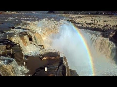 rainbow over northern china waterfall attracts