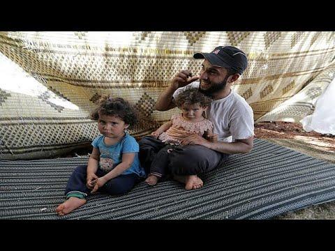 أسرة سورية تجتاز الأراضي الزراعية سيرًا على الأقدام