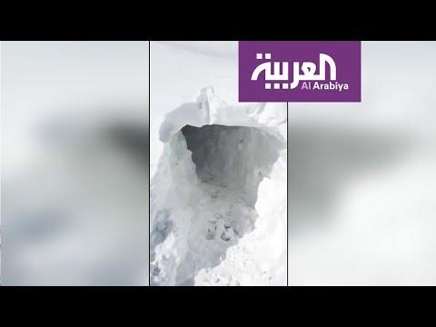 شاهد عراقيون يحفرون أنفاقا في الثلوج للوصول إلى منازلهم